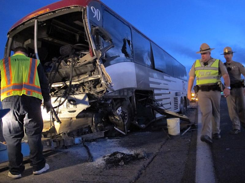 Police inspect a tour bus on the side of Interstate 10 about 50 miles south of Phoenix following a head-on collision with a pickup truck driving the wrong way on Tuesday, Nov. 20, 2012, in Casa Grande, Ariz.  The driver of the pickup truck was killed. Nine people aboard the bus were injured. (AP Photo/Brian Skoloff)