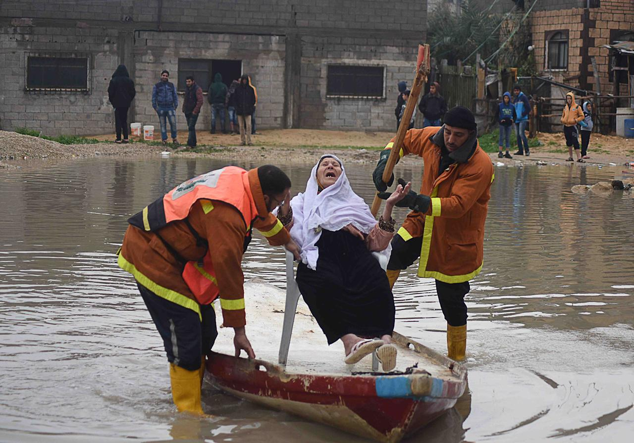 <p>Civil defense team members rescue a woman after heavy rainfall hit Gaza district of al-Saftawi, Gaza on February 16, 2017. (Abed Zagout/Anadolu Agency/Getty Images) </p>
