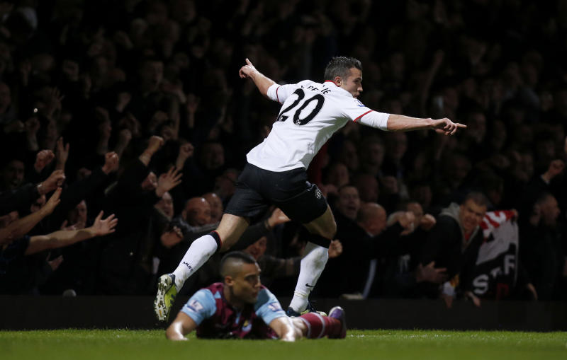 Manchester United's Robin van Persie celebrates his goal as Winston Reid lies on the pitch during the English Premier League soccer match between West Ham and Manchester United at Upton Park stadium in London, Wednesday, April 17, 2013. (AP Photo/Matt Dunham)