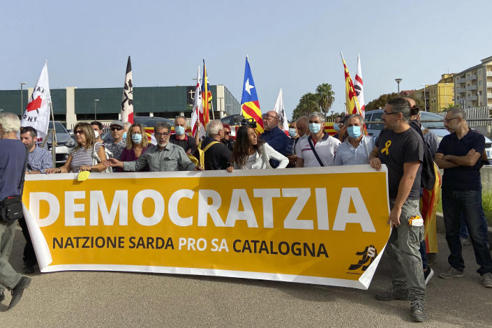 """Demonstrators hold a banner with writing reading in a Sardinian dialect, """"Democracy, the Sardinian nation supports the Catalan nation"""", as they stand outside a court in Sassari, in Sardinia, Italy, Friday, Sept. 24, 2021. Former Catalan leader Carles Puigdemont, sought by Spain for a failed 2017 secession bid, on Friday awaited his opportunity to appear in court to argue against extradition, a day after Italian police detained him in Sardinia, an Italian island with strong Catalan cultural roots and its own independence movement. (AP Photo/Gloria Calvi)"""