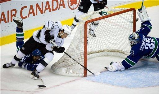 Los Angeles Kings' Jordan Nolan, second left, scores against Vancouver Canucks goalie Cory Schneider as Andrew Alberts, left, defends during the second period of an NHL hockey game in Vancouver, British Columbia on Saturday, March 2, 2013. (AP Photo/The Canadian Press, Darryl Dyck)