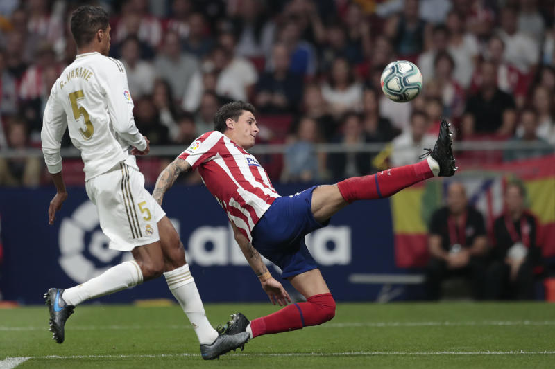 Atletico Madrid's Jose Gimenez, right, and Real Madrid's Raphael Varane vie for the ball during the Spanish La Liga soccer match between Atletico Madrid and Real Madrid at the Wanda Metropolitano stadium in Madrid, Saturday, Sept. 28, 2019. (AP Photo/Bernat Armangue)
