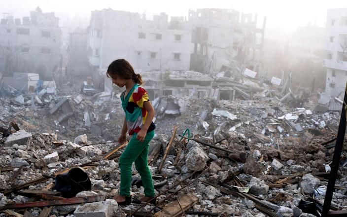 A Palestinian girl walks on the rubble-strewn ceiling of her family's home in Gaza City in 2014 - ROBERTO SCHMIDT /AFP