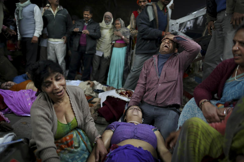 An Indian man weeps as he and other family members mourn next to the body of a relative who was killed in a stampede on a railway platform at the main railway station in Allahabad, India, Sunday, Feb. 10, 2013. At least ten Hindu pilgrims attending the Kumbh Mela were killed and more then thirty were injured in a stampede on an overcrowded staircase, according to Railway Ministry sources. (AP Photo/Kevin Frayer)