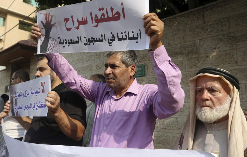 """Families of Palestinians held in jails in Saudi Arabia, hold placards in Arabic that read, """"Release our sons in Saudi prisons, and No for the policy of isolation and torture for the prisoners in Saudi jails"""" during a protest, in front of the International Committee of the Red Cross office, in Gaza, Wednesday, Oct. 16, 2019. (AP Photo/Adel Hana)"""