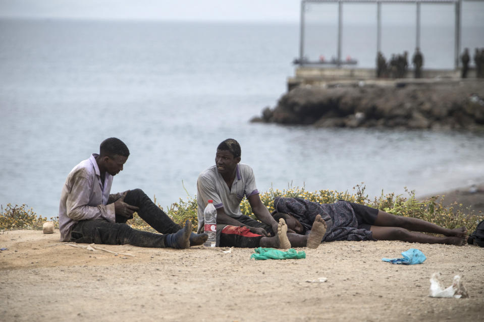 Men sit on the ground after arriving in the Spanish territory at the border of Morocco and Spain, at the Spanish enclave of Ceuta, on Tuesday, May 18, 2021. Ceuta, a Spanish city of 85,000 in northern Africa, faces a humanitarian crisis after thousands of Moroccans took advantage of relaxed border control in their country to swim or paddle in inflatable boats into European soil. Around 6,000 people had crossed by Tuesday morning since the first arrivals began in the early hours of Monday, including 1,500 who are presumed to be teenagers. (AP Photo/Javier Fergo)