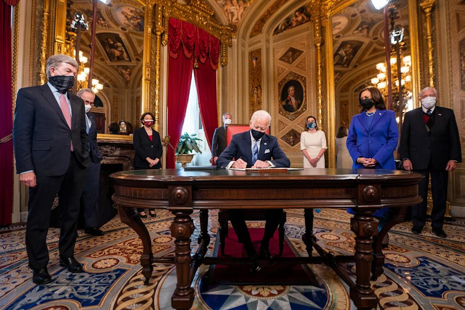 Joe Biden signs three documents including an inauguration declaration, cabinet nominations, and sub-cabinet nominations in the President's Room at the Capitol AP