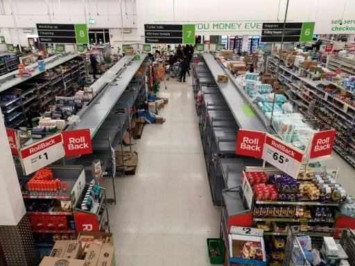 Empty shelves are pictured in the toilet roll/kitchen towel aisle of a supermarket in London on March 13, 2020