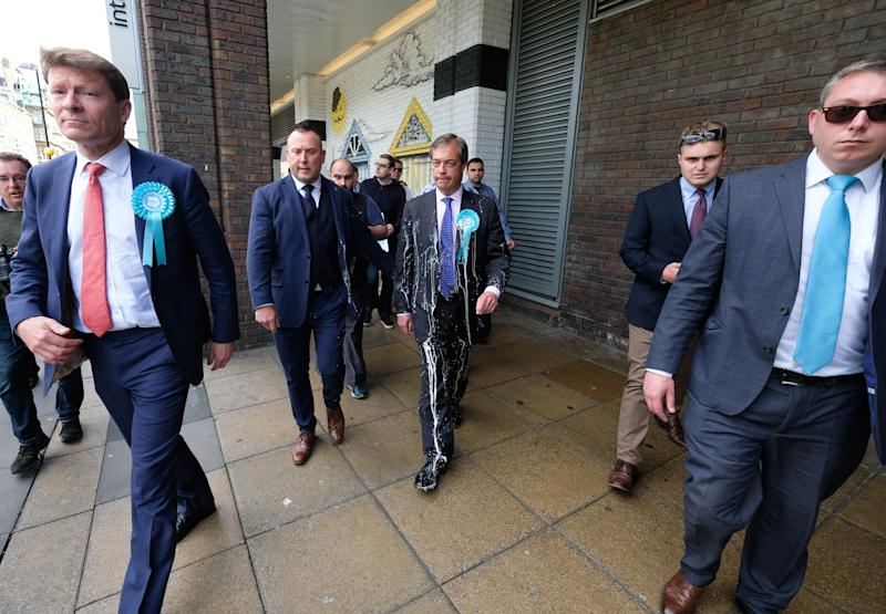 NEWCASTLE-UPON-TYNE, ENGLAND - MAY 20: Brexit Party leader Nigel Farage is escorted to a car after having what is thought to be milkshake thrown over him as he visits Northumberland Street in Newcastle Upon Tyne during a whistle stop UK tour on May 20, 2019 in Newcastle Upon Tyne, England. The visit to Newcastle comes ahead of the 2019 European elections in the United Kingdom which will take place on May 23. The Brexit Party is a pro-Brexit Eurosceptic political party formed in 2019. Nigel Farage, the former leader of the U.K. Independence Party, is campaigning for the Brexit Party's contest for this month's European Parliament elections. The Brexit Party is reported to be polling in front of Labour and the Conservatives for the European parliament elections. (Photo by Ian Forsyth/Getty Images)