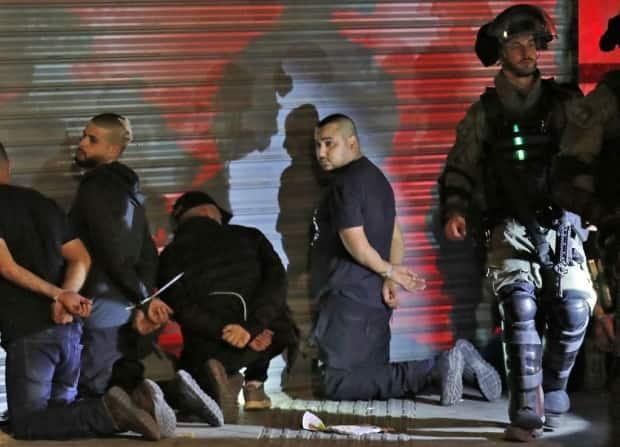 Israeli forces detain a group of Arab Israelis in the mixed Jewish-Arab city of Lod after they clashed with Israeli far-right extremists.