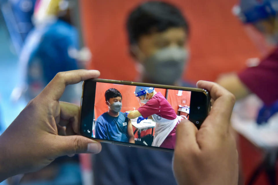 A father records his son receiving the Covid-19 vaccination at the Labuan Matriculation College vaccination centre, September 24, 2021. — Bernama pic