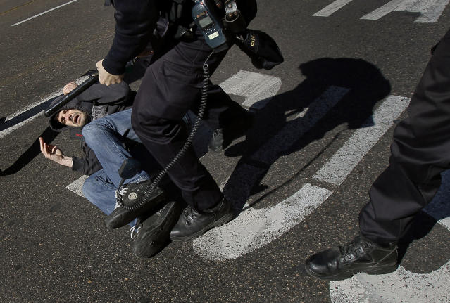<p>A protester is grabbed by police in Madrid, March 29, 2012, during a general strike. Flag-waving Spanish workers angered by reforms they see as flagrantly pro-business blocked traffic, formed boisterous picket lines outside wholesale markets and bus garages, and kept some TV programming off the air. (AP Photo/Andres Kudacki) </p>