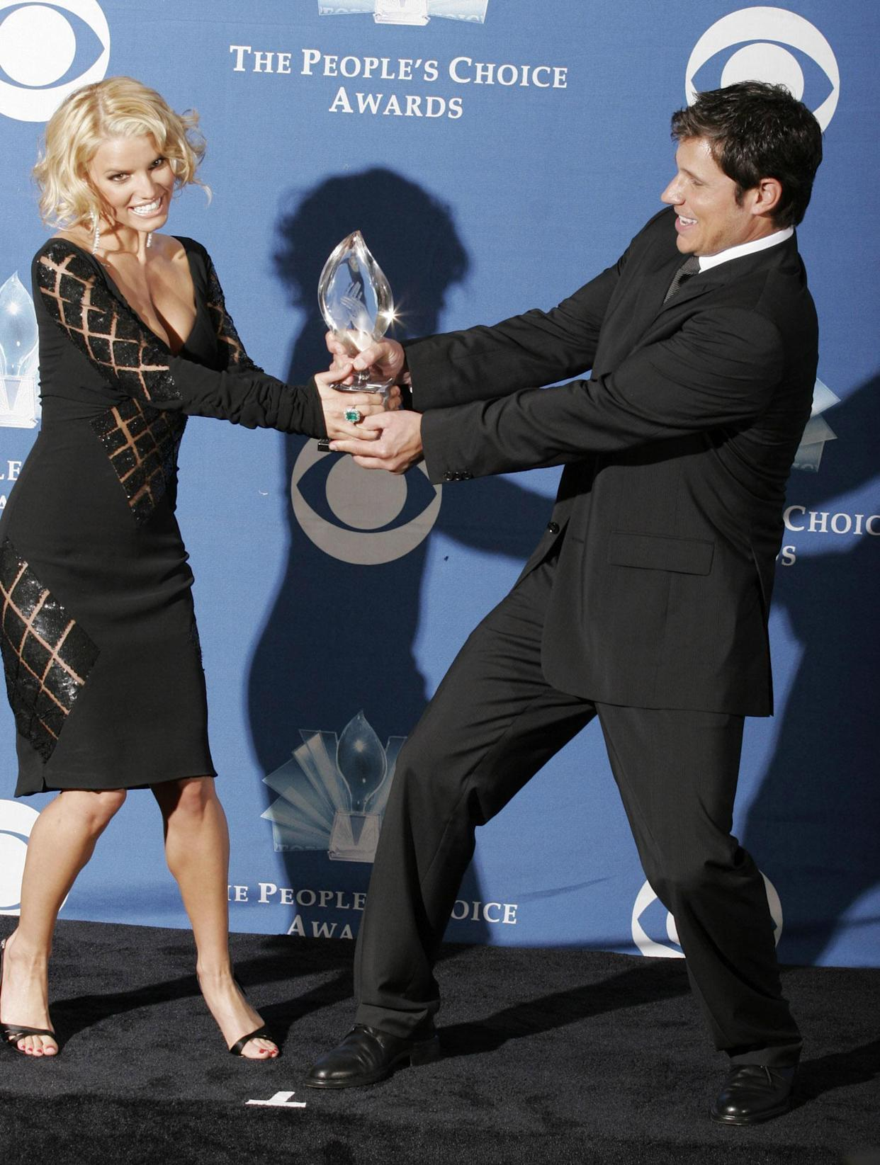 Jessica Simpson and her husband Nick Lachey have a playfight over their Favorite Reality-Based Program award for 'Newlyweds' at the 2005 People's Choice Awards. (Photo: Francis Specker - PA Images/PA Images via Getty Images)