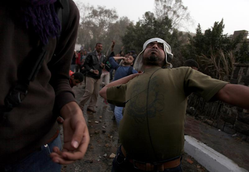 An Egyptian protester throws a stone during clashes between supporters and opponents of Egypt's powerful Muslim Brotherhood near the Islamist group's Cairo, Egypt headquarters Friday, March 22, 2013. (AP Photo/Khalil Hamra)