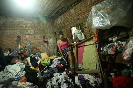 Ximena, 26, an indigenous Zapotec transgender woman also know as Muxe, walks on her belongings inside her house destroyed after an earthquake that struck on the southern coast of Mexico late on Thursday, in Juchitan, Mexico, September 10, 2017. REUTERS/Edgard Garrido