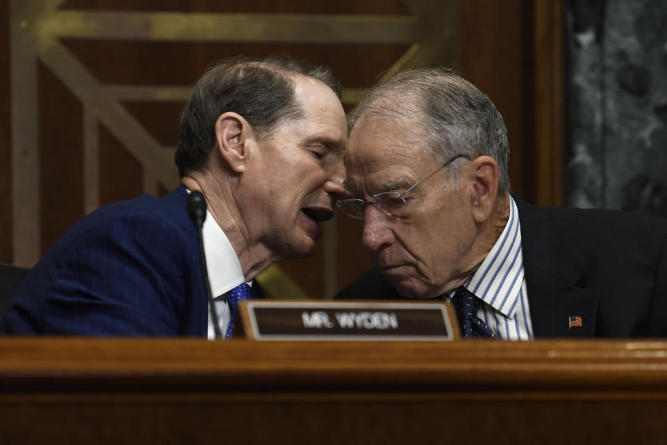 FILE - In this Tuesday, June 18, 2019, file photo, Senate Finance Committee ranking member Sen. Ron Wyden, D-Ore., left, talks with committee chairman Sen. Chuck Grassley, R-Iowa, during a hearing on Capitol Hill in Washington. A bipartisan congressional investigation released Wednesday, Dec. 16, 2020, by Grassley and Wyden, found that key players in the nation's opioid industry have spent $65 million since 1997 funding nonprofits that advocate treating pain with medications, a strategy intended to boost the sale of prescription painkillers. (AP Photo/Susan Walsh, File)