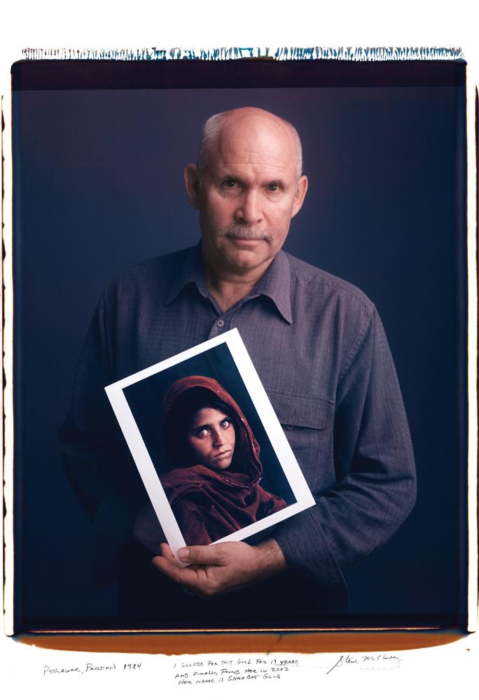 "Photographer Tim Mantoani has captured famous photographers posing with their most iconic images for his new book 'Behind Photographs: Archiving Photographic Legends'. <br> <br> Pictured here: Steve McCurry - ""I looked for this girl for 17 years and finally found her in 2002. Her name is Sharbat Gula."" <br> <br> Photo: Tim Mantoani"