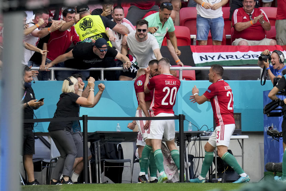 Hungary's Attila Fiola celebrates with teammate Roland Sallai, number 20, after scoring his side's opening goal during the Euro 2020 soccer championship group F match between Hungary and France, at the Ferenc Puskas stadium in Budapest, Saturday, June 19, 2021. (AP Photo/Darko Bandic, Pool)