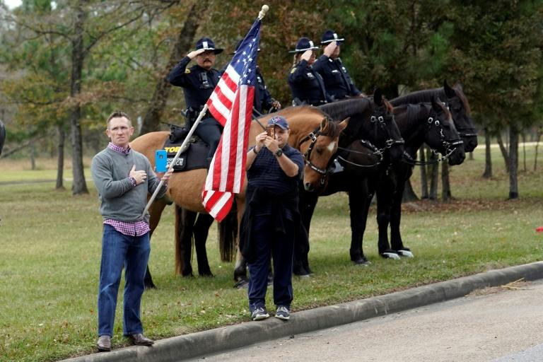 People line the road as the hearse carrying the flag-draped casket of former US president George H.W. Bush heads to a Houston train station, for a final trip to the late leader's presidential library