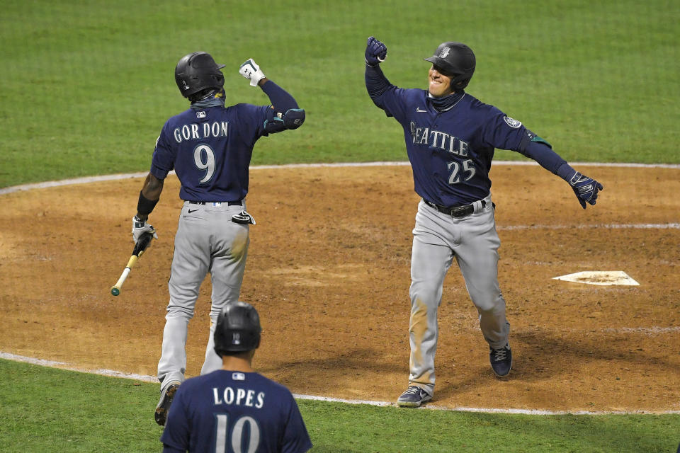 Seattle Mariners' Dylan Moore, right, is congratulated by Dee Gordon, left, after hitting a three-run home run as Tim Lopes watches during the sixth inning of a baseball game against the Los Angeles Angels Wednesday, July 29, 2020, in Anaheim, Calif. (AP Photo/Mark J. Terrill)