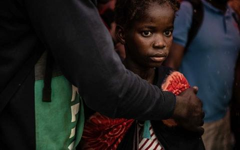 A young girl stares into the distance as people from the town of Buzi unload at Beira Port after being rescued yesterday - Credit:  Andrew Renneisen/ Getty