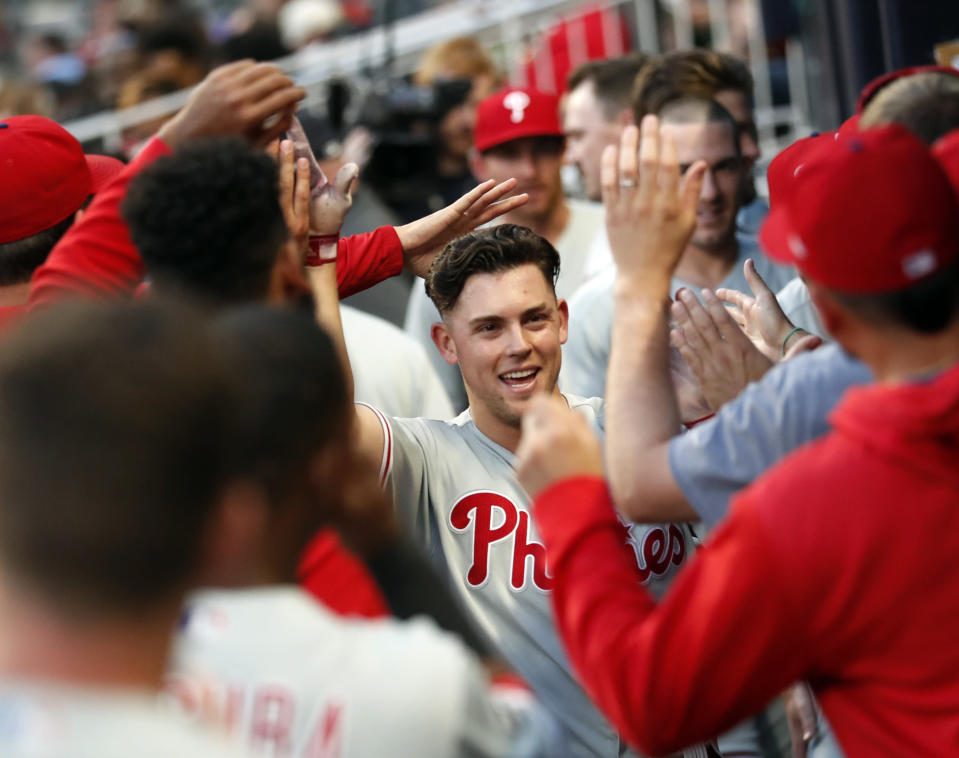 Philadelphia Phillies' Scott Kingery is greeted in the dugout after hitting a solo home run in the fourth inning of the team's baseball game against the Atlanta Braves on Friday, June 14, 2019, in Atlanta. (AP Photo/John Bazemore)