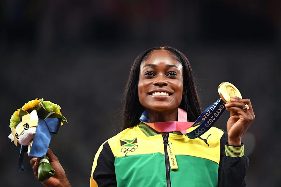 Gold medallist Jamaica's Elaine Thompson-Herah celebrates during the medal ceremony for the women's 200m event during the Tokyo 2020 Olympic Games at the Olympic Stadium in Tokyo on August 4, 2021. (Photo by Ina FASSBENDER / AFP) (Photo by INA FASSBENDER/AFP via Getty Images)