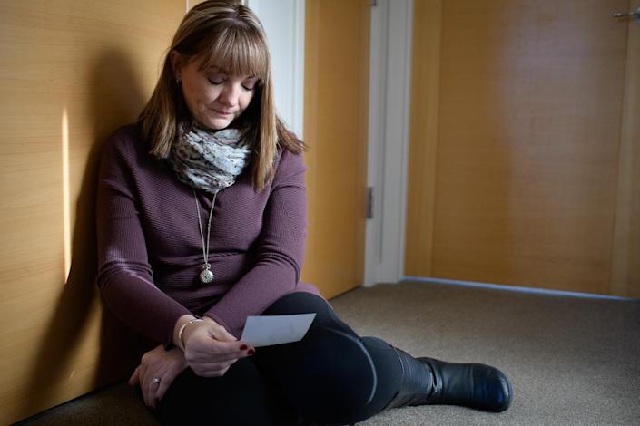"""Coni Sanders looks at a photo of her father, William """"Dave"""" Sanders, who was killed in the Columbine shooting. (Photo: Carl Bower for Yahoo News)"""