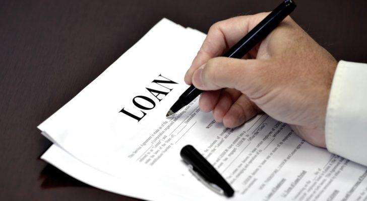 Image of a hand signing a paper with the loan as the title