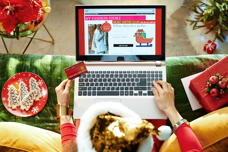 Holiday season. stylish female in sparkle gold sequin santa hat with credit card shopping clothes while using ecommerce site on a laptop while sitting on couch in the modern living room at Christmas.