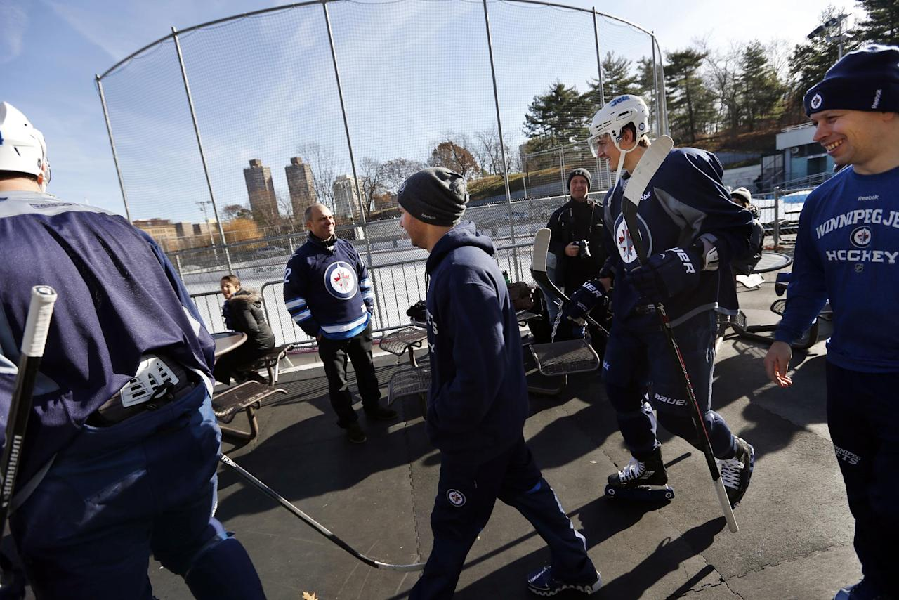 A fans looks on as members of the Winnipeg Jets walk to the ice for an outdoor NHL hockey practice at Lasker Rink in New York's Central Park, Saturday, Nov. 30, 2013. (AP Photo/Jason DeCrow)