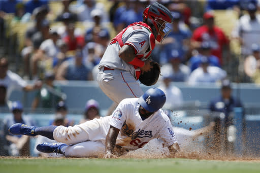 Los Angeles Dodgers Andrew Toles scores in front of Los Angeles Angels catcher Martin Maldonado on a sacrifice fly ball hit by Dodgers Enrique Hernandez during the second inning of a baseball game Sunday, July 15, 2018, in Los Angeles. (AP Photo/Danny Moloshok)