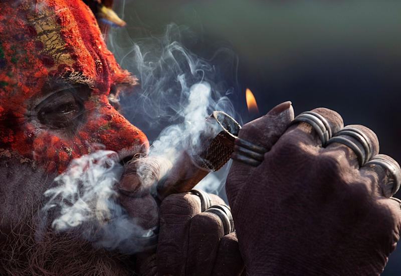 A sadhu, or holy man, smokes marijuana from a clay pipe at the Pashupati Temple in Kathmandu, Nepal, March 4, 2019, during celebrations marking the Hindu festival of Maha Shivaratri. (Photo: Narendra Shrestha/EPA-EFE/REX/Shutterstock)