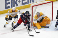 Nashville Predators' Alexandre Carrier, left, tries to stop Columbus Blue Jackets' Cam Atkinson, center, from taking a shot against Nashville Predators' Juuse Saros during the first period of an NHL hockey game Monday, May 3, 2021, in Columbus, Ohio. (AP Photo/Jay LaPrete)