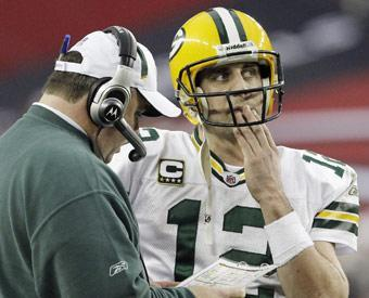 Packers coach Mike McCarthy talks with Rodgers during the first half