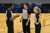 Referees from left, Sean Wright, Natalie Sago and Jenna Schroeder have a discussion during a time out in the second half of an NBA basketball game between the Orlando Magic and the Charlotte Hornets, Monday, Jan. 25, 2021, in Orlando, Fla. Natalie Sago and Jenna Schroeder made up two-thirds of the crew assigned to the Charlotte at Orlando game, the first time in NBA history that two women were assigned to work a regular-season contest together.(AP Photo/John Raoux)
