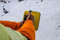 A rescue worker uses an electronic detector to try to locate the missing trekkers