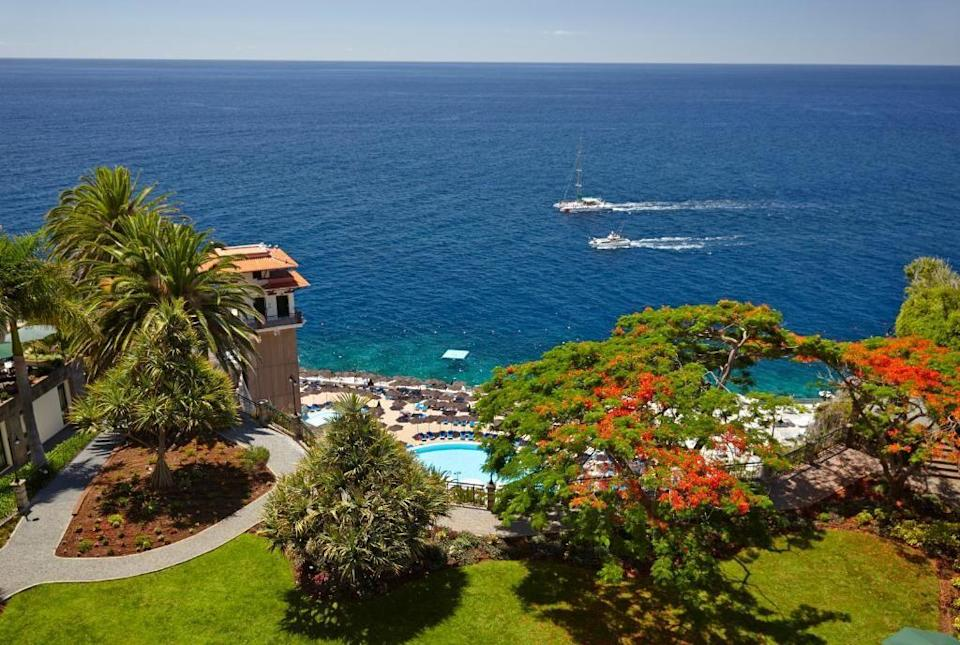 """<p>One of Madeira's finest resort hotels, the five-star <a href=""""https://go.redirectingat.com?id=127X1599956&url=https%3A%2F%2Fwww.booking.com%2Fhotel%2Fpt%2Fthe-cliff-bay.en-gb.html%3Faid%3D1922306%26label%3Dmadeira-hotels&sref=https%3A%2F%2Fwww.goodhousekeeping.com%2Fuk%2Flifestyle%2Ftravel%2Fg37065833%2Fmadeira-hotels%2F"""" rel=""""nofollow noopener"""" target=""""_blank"""" data-ylk=""""slk:Cliff Bay"""" class=""""link rapid-noclick-resp"""">Cliff Bay</a> rises elegantly from a peninsula above Funchal and boasts unbeatable views of the sparkling Atlantic ocean, indoor and outdoor pools, a full-service spa, tennis courts, private sea access, and Madeira's only two Michelin star restaurant, Il Gallo d'Oro. </p><p>Overseen by French chef Benoît Sinthon since 2004, it presents artful Iberian dishes made with produce grown in the hotel's own gardens – making the most of Madeira's wonderful climate. Inside, the bedrooms are spacious, modern and comfortable, and all have private balconies that either overlook the gardens or offer spectacular views of the bay.</p><p><a class=""""link rapid-noclick-resp"""" href=""""https://go.redirectingat.com?id=127X1599956&url=https%3A%2F%2Fwww.booking.com%2Fhotel%2Fpt%2Fthe-cliff-bay.en-gb.html%3Faid%3D1922306%26label%3Dmadeira-hotels&sref=https%3A%2F%2Fwww.goodhousekeeping.com%2Fuk%2Flifestyle%2Ftravel%2Fg37065833%2Fmadeira-hotels%2F"""" rel=""""nofollow noopener"""" target=""""_blank"""" data-ylk=""""slk:CHECK AVAILABILITY"""">CHECK AVAILABILITY</a></p>"""