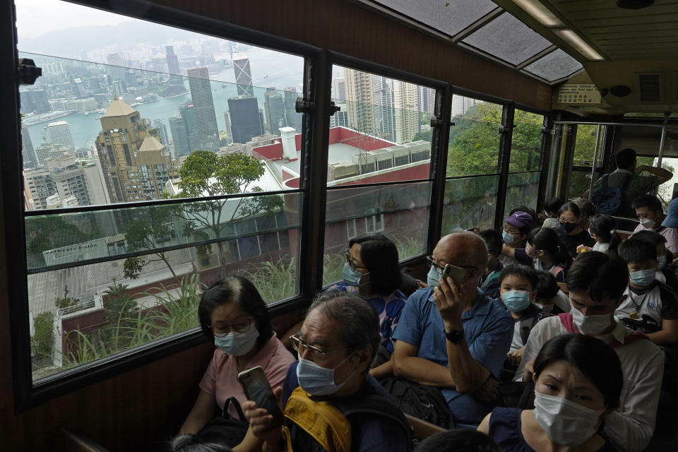 Passengers enjoy a view from the cabin as a Peak Tram goes downhill of the Victoria Peak in Hong Kong on June 17, 2021. Hong Kong's Peak Tram is a fixture in the memories of many residents and tourists, ferrying passengers up Victoria Peak for a bird's eye view of the city's many skyscrapers. (AP Photo/Vincent Yu)