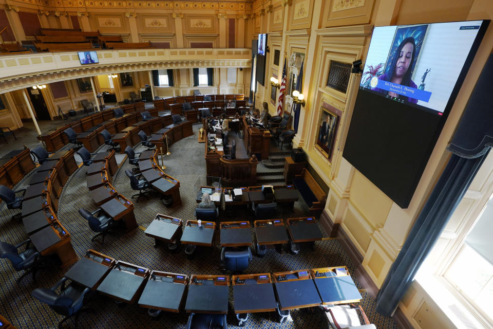 House speaker Del. Eileen Filler-Corn, D-Fairfax, at rostrum, listen as House majority leader, Del. Charniele Herring, D-Alexandria, on monitor, speaks in an empty Virginia House of Delegates chamber during a Zoom Legislative session at the Capitol in Richmond, Va., Wednesday, Feb. 10, 2021. (AP Photo/Steve Helber)