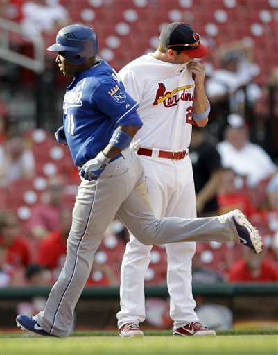 Kansas City Royals' Yuniesky Betancourt, front, rounds the bases past St. Louis Cardinals third baseman David Freese after hitting a two-run home run during the 15th inning of a baseball game on Sunday, June 17, 2012, in St. Louis. The Royals won 5-3. (AP Photo/Jeff Roberson)