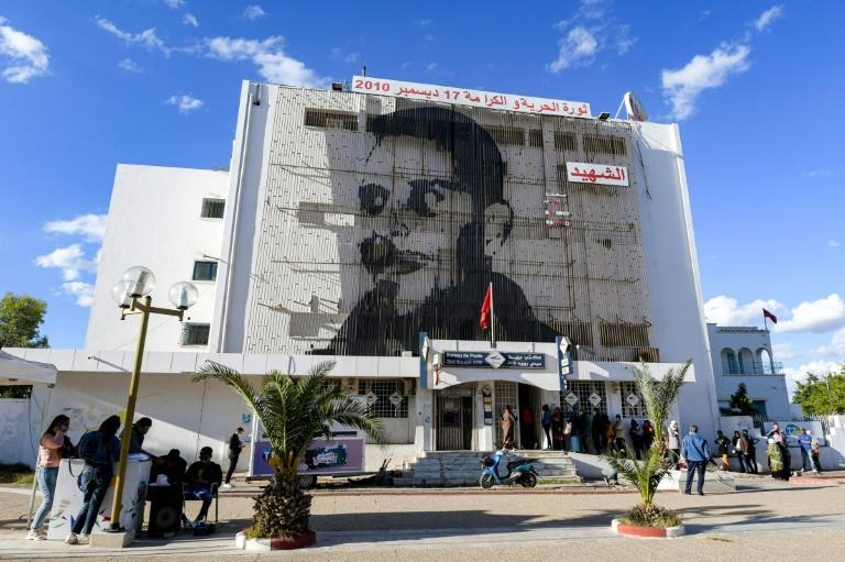 People queue up outside the main post office on Mohamed Bouazizi Square, its facade displaying a picture of Bouazizi, who set himself on fire ten years ago