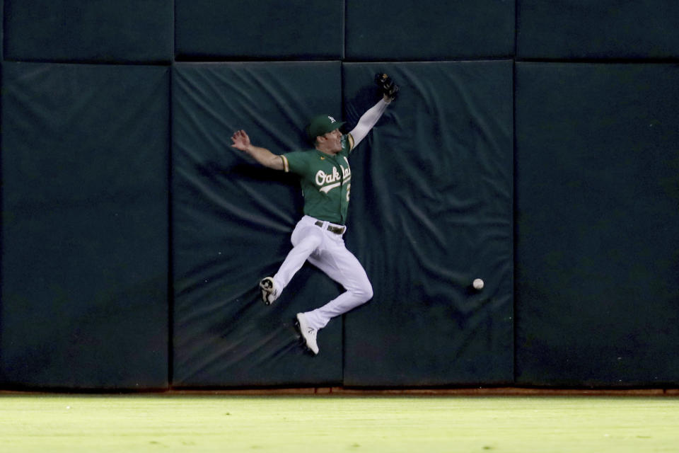 Oakland Athletics' Mark Canha crashes into the outfield wall on a triple hit by Seattle Mariners' Dylan Moore during the fourth inning of a baseball game in Oakland, Calif., Tuesday, Sept. 21, 2021. (AP Photo/Jed Jacobsohn)