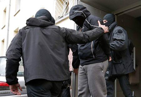 French special Police forces escort a suspect from a residential building in the Meinau suburb of Strasbourg