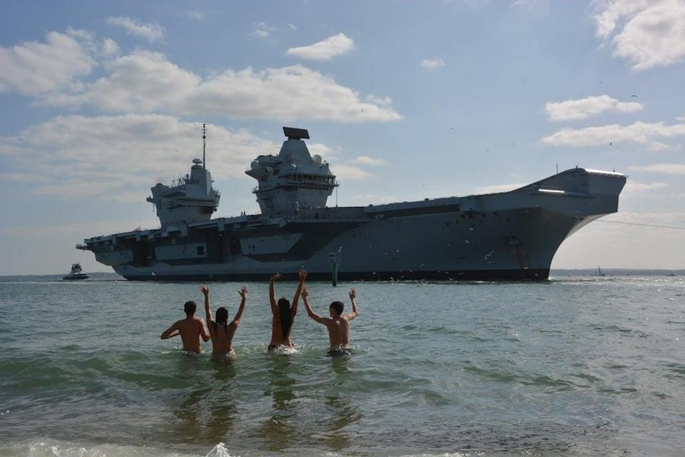 Bathers welcome home the HMS Prince of Wales aircraft carrier to Portsmouth (Ben Mitchell/PA) (PA Wire)