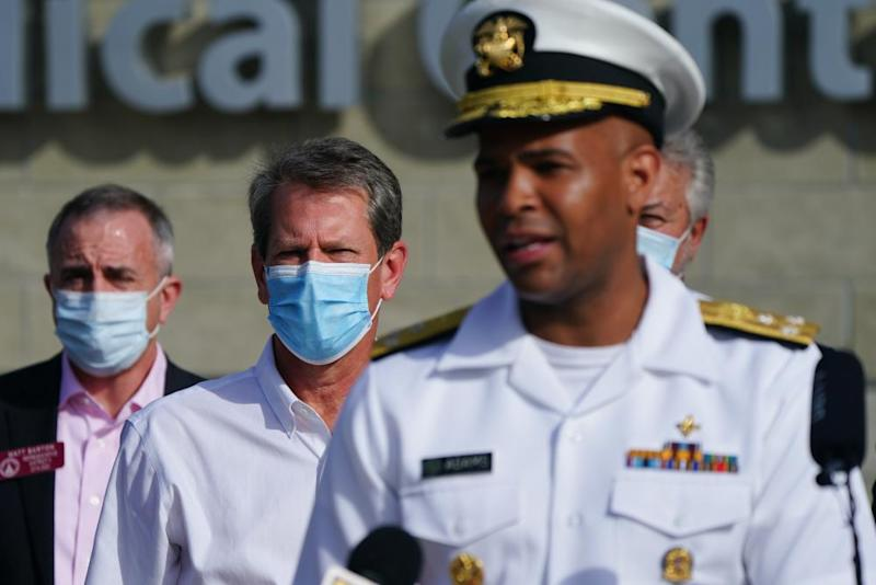 """Brian Kemp, governor of Georgia, center, listens while Vice Admiral Jerome Adams, U.S. Surgeon General, speaks during a 'Wear A Mask' tour stop in Dalton, Georgia, U.S., on Thursday, July 2, 2020. Governor Kemp on Wednesday expressed his skepticism about the need for a statewide mask mandate and his reluctance to impose one, calling it an issue he feels is """"overpoliticized."""""""