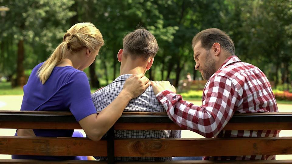 Parents sit on bench with son in the middle, hands are on his shoulder