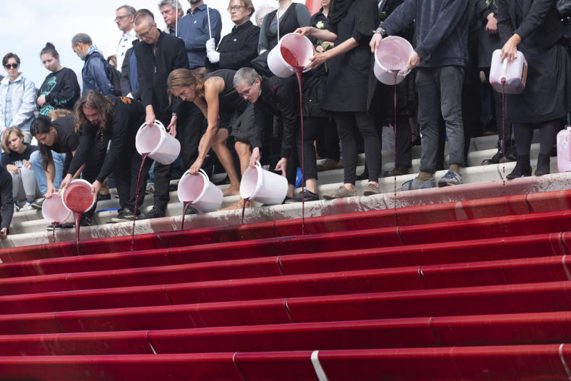 Activists of the group 'Extinction Rebellion' shedding red liquid, symbolizing blood, on the stairs of the recently opened promenade at the Baumwall during the Cruise Days in Hamburg, Germany, Saturday, Sept. 14, 2019. Extinction Rebellion held a protest march on the grounds of the Cruise Days to demonstrate for a better climate policy. (Jonas Walzberg/dpa via AP)