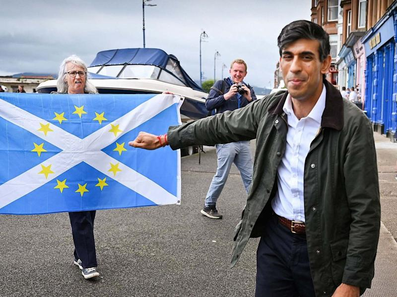 A pro-independence demonstrator holds a flag as she welcomes chancellor Rishi Sunak to Scotland: REUTERS