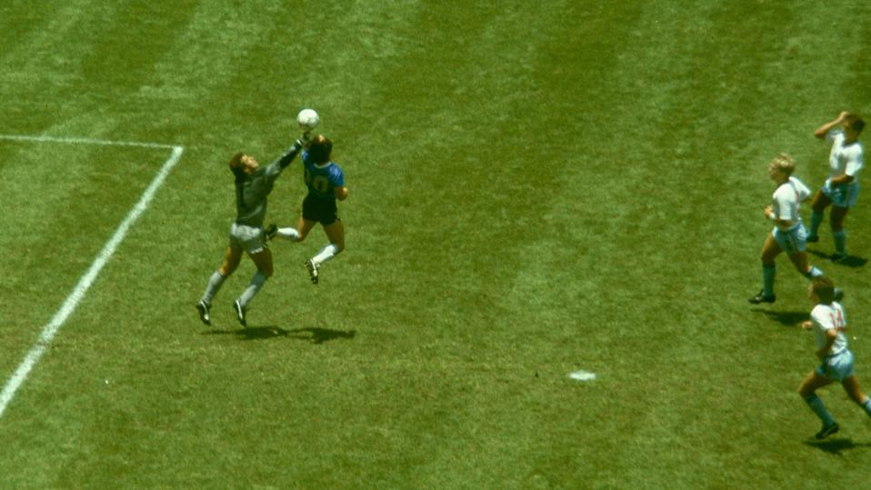 "Diego Maradona outjumps England goalkeeper Peter Shilton to score with his ""Hand of God"" goal at the 1986 World Cup."